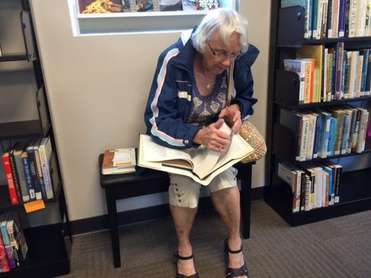 Helen Komplin of Fond du Lac looks through a reference book at Chapter 52, a new used bookstore in downtown Fond du Lac, run by the Fond du Lac Public Library.