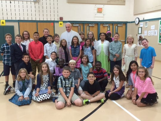 Students at St. Theresa Catholic School pose with a life-sized cutout of Pope Francis.