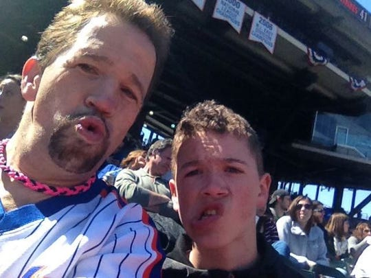 Leslie Gabriel and his son, Jerry, enjoy a Mets game at Citi Field.