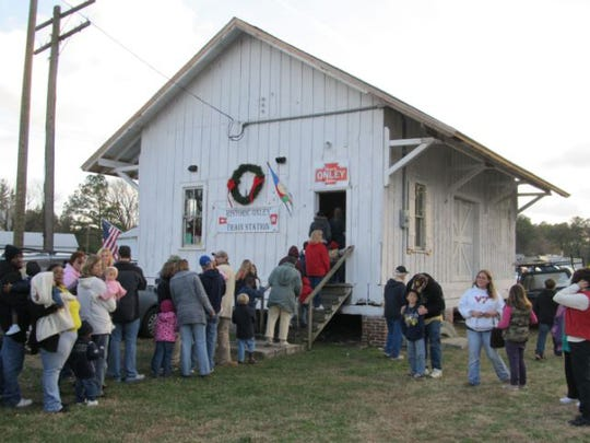 Children and parents wait outside the Onley Train Station to visit with Santa and Mrs. Claus during the Onley stop of the annual Santa Train.