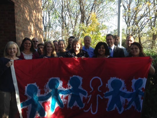 The Child Advocacy Center raised a flag on Wednesday, November 11, for the 1,931 children who have been victims of child abuse in 2015.  Pictured:  Aleta Tuma, Amanda Pruitt, General Bill Whitesell, Kim Snell, Beth Parker, Sgt. Sheree Robertson, Claire Tuma, Caitlyn Brown, Sharon De Boer, Terry Fann, Christina Moody, General Jennings Jones, Ryan Wallace, Sgt. Paul Mongold, and Jessica Wauchek.