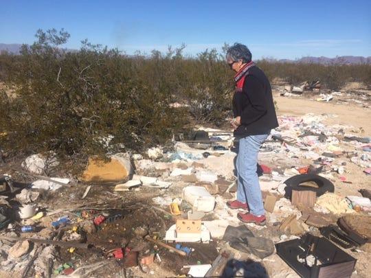 Martha Home walks through garbage dumped in the desert