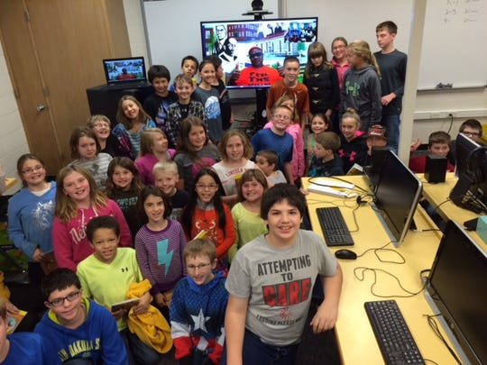 Dapo Akers is shown on the screen in back during a reading session by Skype for students in Lake Benton, Minn.