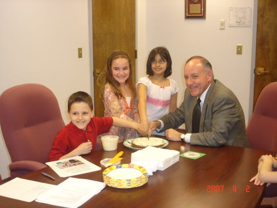 Third-graders with a cake they made for Monroe Mayor
