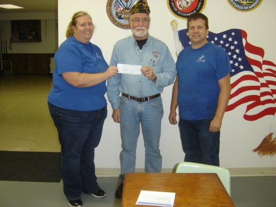 VFW Post 2534 Commander Tom Sachs, center, receives a check from J Squared Catering owners Julie and Joel Flewellen.