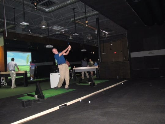 Participants take turns at XGolf,  an indoor, virtual  golf bar that will open in Lafayette soon.