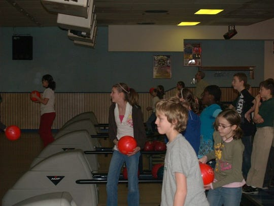 Young bowlers having fun at Midway Lanes. The youth bowling program is held every Saturday morning.