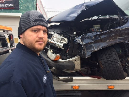 Darryn S. Shipton stands in front of his Chevy Tahoe,