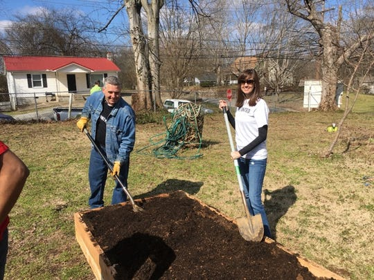 Local United Way President Shannon Green, left, and Executive Director Ginna Holleman shovel in some dirt for one of the raised beds.