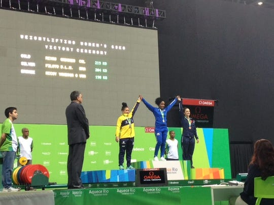 USA Weightlifting's Vanessa McCoy, right, stands on the podium to accept her bronze medal at a pre-Olympics event in Rio de Janeiro.