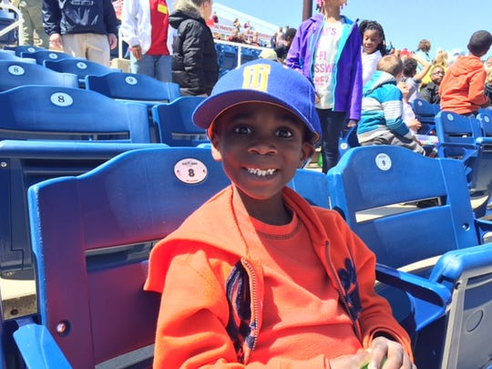 Southern Elementary School second-grader Elijah Jackson watches Wednesday's Blue Rocks game from behind the visiting dugout.