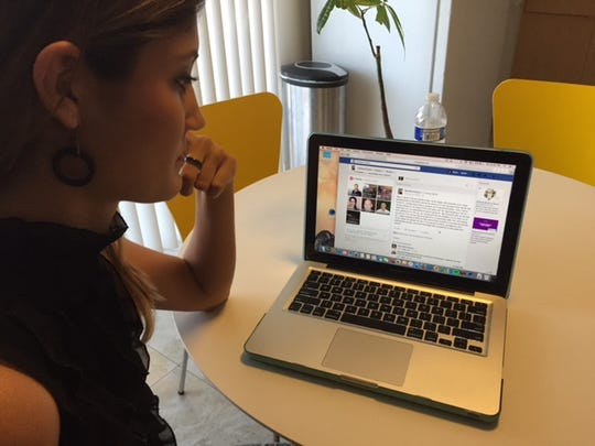 Erica Harnik looks at a Facebook post her coworker,