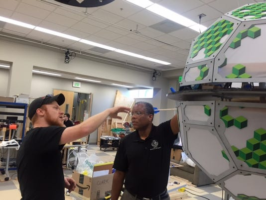 635989241618266236-Post-doctorial-Mechaicial-Engineering-student-Tyler-Jonas-showing-Director-Emmanuel-Collins-a-Mecatronics-in-Art-class-project.JPG
