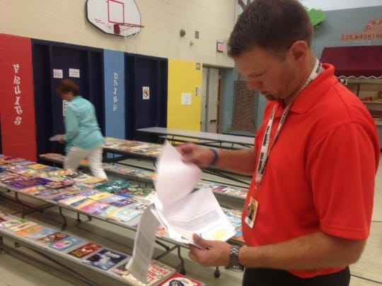 Paul Murphy, a third-grade teacher at Washington Elementary School in Charlotte, pages through a list of students chosen for the Summer Books reading program.