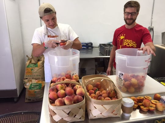 Roby Hubbard, left and Jeremy Elrod, right, perp peaches for fresh popsicles.