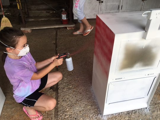 Catherine Hammons paints a newspaper machine as part of a service project her Girl Scout troop is doing.