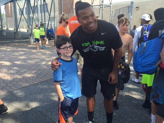 Marcus Burley poses for a photo with a UD football camper.