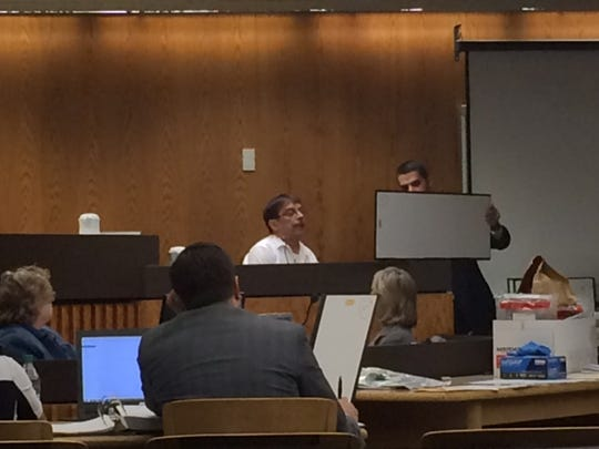Michael Brantner looks at cell phone records shown to him by Fond du Lac County District Attorney Eric Toney on Thursday at the murder trial of his brother, Dennis Brantner.