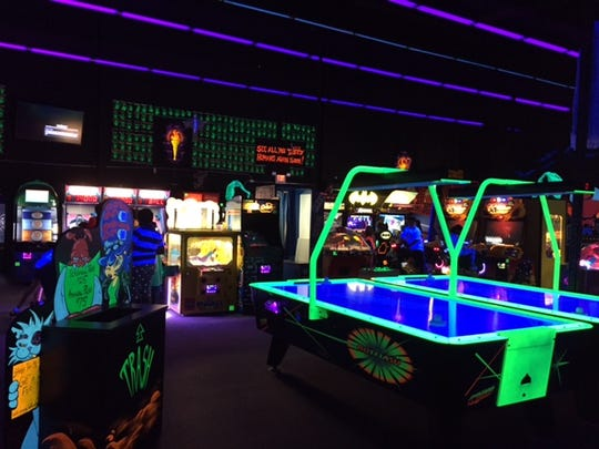 Even air hockey gets the glow-in-the-dark treatment in the arcade at Monster Mini Golf in Eatontown.