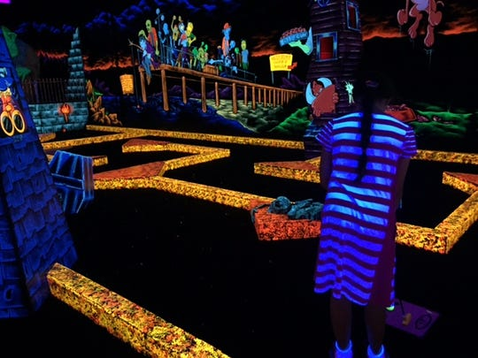 The long and winding course at Monster Mini-Golf is made more challenging by darkness.