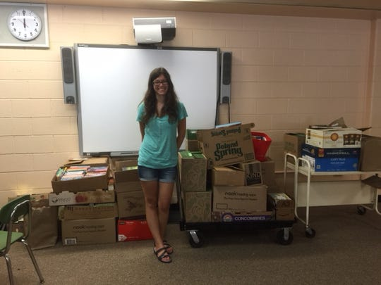 Moorestown's Nori Horvitz stands with boxes of books being donated to the R.T. Cream Elementary School in Camden last summer after a Bookitcon charity event. Bookitcon: Chapter Two is Sunday at The Moorestown Community House.