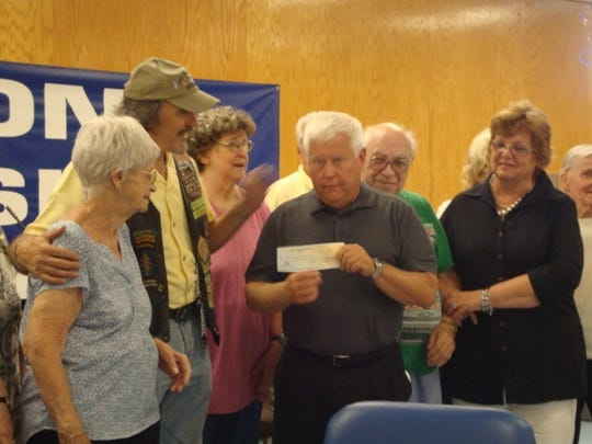 John Welgos, president of the Patriot Brothers Chapter of the Nam Knights Motorcycle Club, Jay Elliot, director of Health and Human Services, and Judi Gillingham, assistant director for aging, Township of Edison, are surrounded by seniors from the Edison Senior Center during a recent check presentation.