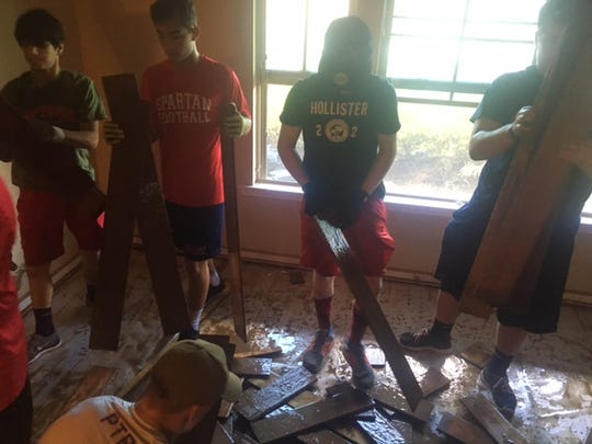 Comeaux High football players help clean up homes that were damaged by flood.