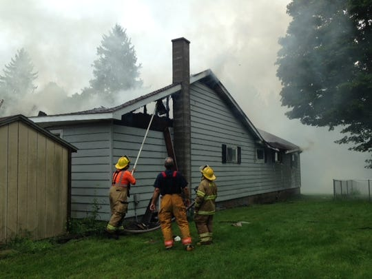 Firefighters work on a blaze at 6412 2-Mile Road in Leroy Township on Thursday.