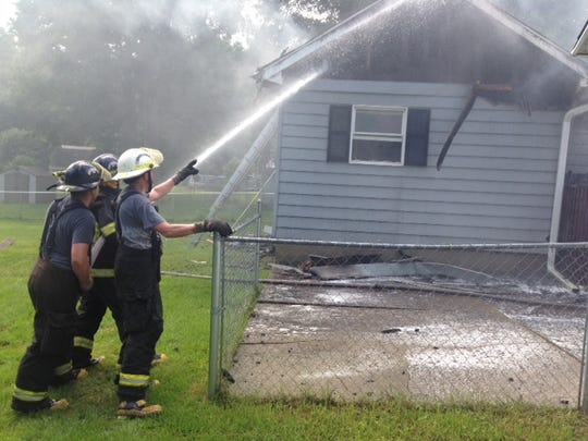 Firefighters pour water on a hot spot after fire destroyed much of a house on 2-Mile Road in Leroy Township on Thursday morning.