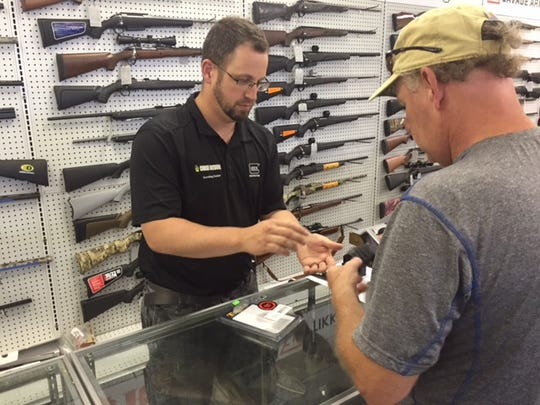 Justin Gaiche, owner of Chase Outdoors, helps a customer