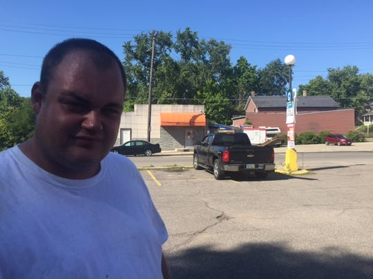 Matt Belcher stands in the business he runs, the Orange Street Market, across from his late father's bar, Belcher's House of Rock at 185 Orange St.