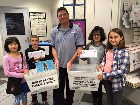 Maggie Samudio's second-grade class prepares to mail letters asking people to support their petition to adopt the Say's firefly as Indiana's state insect. Kayla Xu, left, came up with the idea.