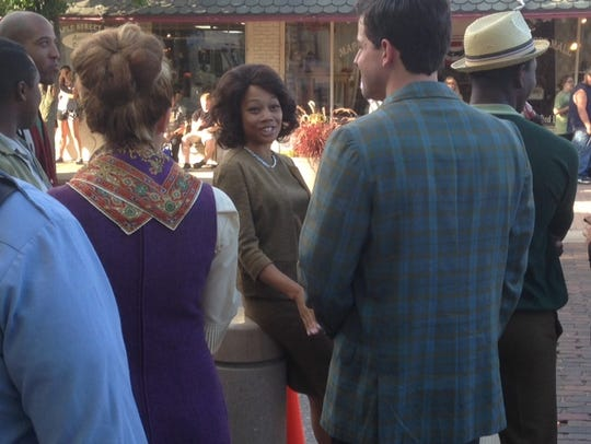 Actors in 1960s attire relax in  downtown Mason on