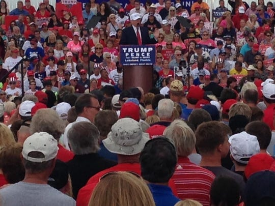 A large crowd listens as Donald Trump speaks at a rally