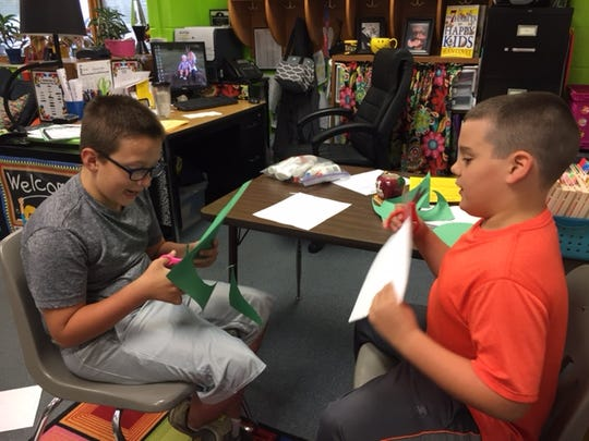 A.B. Chandler fourth-graders Trey Roy, left, and Korey Baxter cut construction paper for their monster glyph on Oct. 20, 2016.