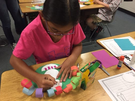 A. B. Chandler Elementary fourth-grader Sarah LaFlair colors her monster glyph on Oct. 20, 2016 during a house meeting.