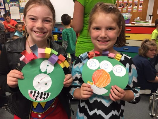 A.B. Chandler Elementary fifth-grader Alya Fossum, left, and first-grader Ellyson Sagez, right, show off their monster glyphs they made at a house meeting on Oct. 20, 2016.
