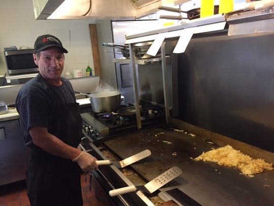 Louie Mena prepares hash browns for breakfast on October