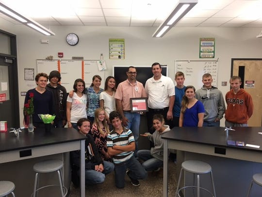 Capitan High School science teacher Christopher Scott, holding certificate, poses with Brandon Stokes and his students.
