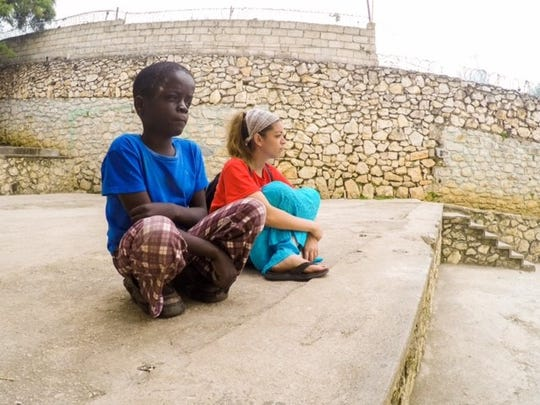 Nicole Tirado sits with a 17- year old mentally disabled orphan rescued of the streets of Haiti.