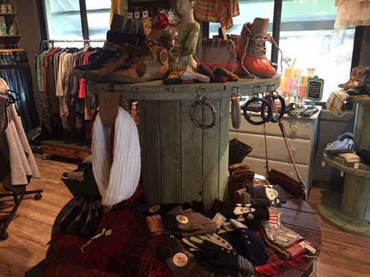 A selection of boots, socks and winter accessories adorns the center of the small boutique.