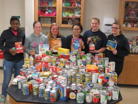 Reedsville students pose with some of the food items a district-wide canned food drive collected in November.