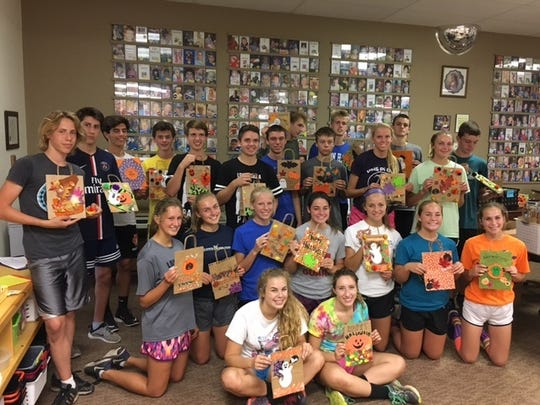 Members of the Plymouth High School cross country team display Halloween bags they decorated for Project Angel Hugs.