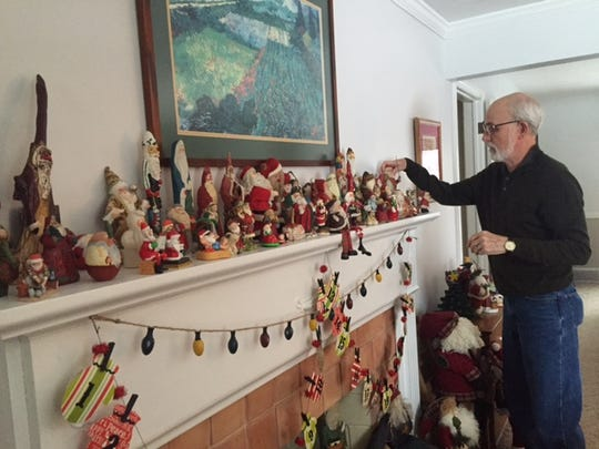 Dave and Terri Remy have collected Santas from vacations along with some carved by Dave's late father Lewis. The Santas range in size from an inch to 5 feet tall. Dave adjusts one of the miniature Santas on the couple's mantle on Fairlawn Avenue.