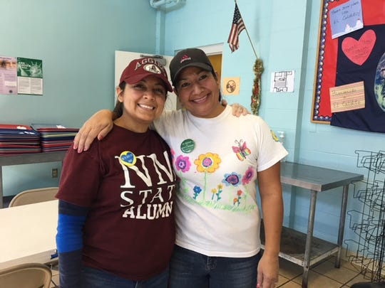 Desma Montellano, left, and Nohemi Perez smile after a day of volunteering at El Caldito soup kitchen. A number of volunteers from New Mexico State University recently volunteered at El Caldito in memory of staff member Ann Palormo, who died in in November.