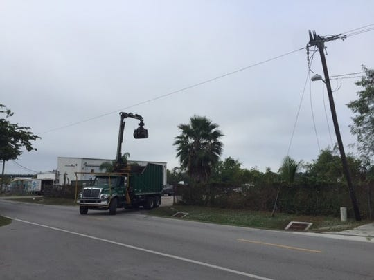 A truck crashed into power lines in an industrial park in North Naples and officials are looking at turning off power in the area to free the driver, officials said.