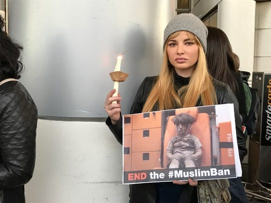 Ashley Rickards, of Los Angeles, holds a candle and a sign Saturday night at Los Angeles International Airport, where a crowd gathered to protest President Donald Trump's ban on immigrants from several mainly Muslim countries.