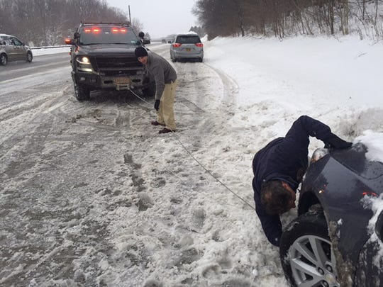 Gov. Andrew Cuomo is shown attaching a tow line onto a vehicle stranded on the side of the Sprain Brook Parkway near Hawthorne. The photo was posted to Twitter by Cuomo's chief of staff.
