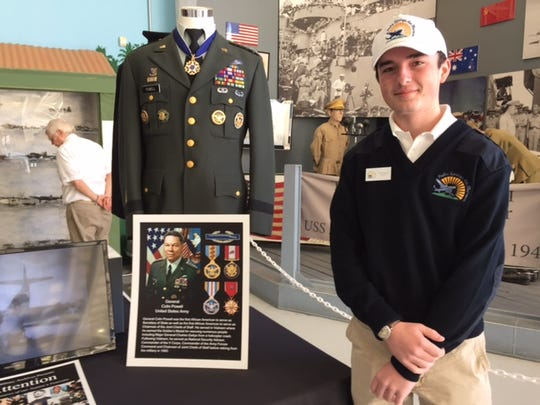 Will Twomey stands next to a U.S. Army uniform worn by General Colin Powell. The teen had some of his uniform collection on display recently at the Palm Springs Air Museum.