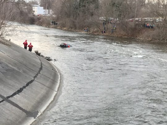 A car is pulled from the bottom of the Kalamazoo River on Sunday.